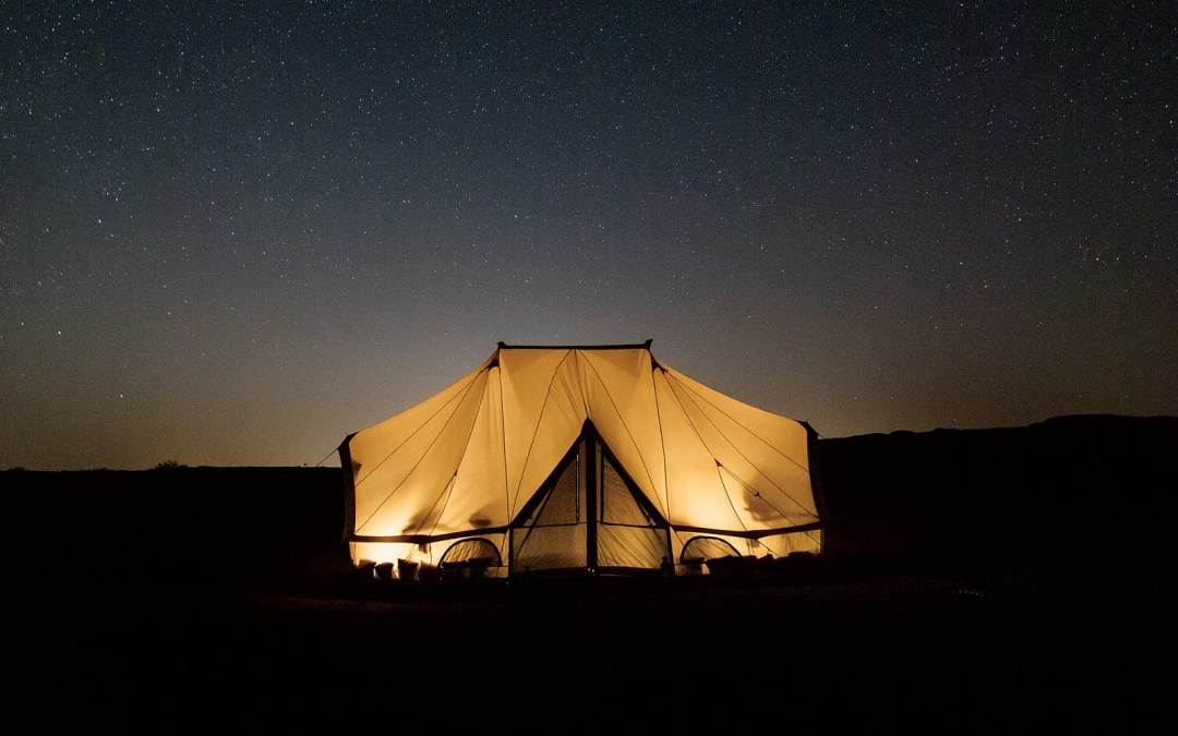 Lighted tent under starry night sky in Oman