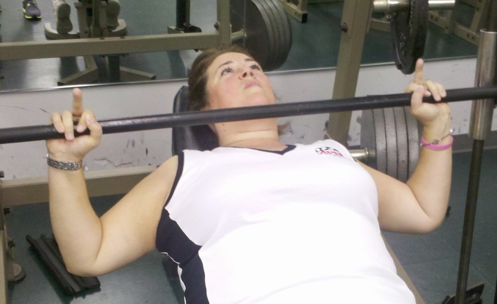 Fitness female personal trainer weight lifting