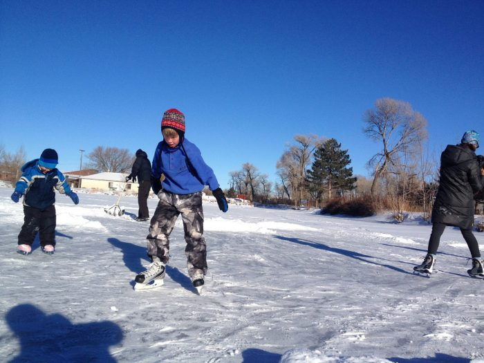 Kids ice skating on a pond in Montana