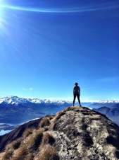 Distant shot of Tayler standing on the top of Roy's Peak in Wanaka, New Zealand overlooking the beautiful mountain landscape