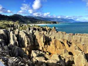 The pancake rocks with the ocean and small mountains in the distance in new zealand