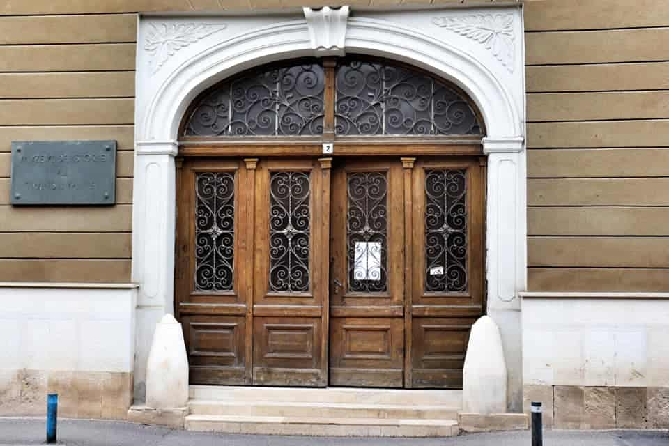 Entrance to Ethnography Museum in Cluj Napoca, two large wooden doors.