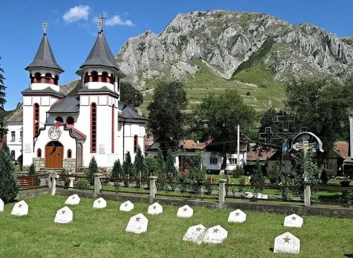 Church in Rimetea, Transylvania with mountain backdrop.