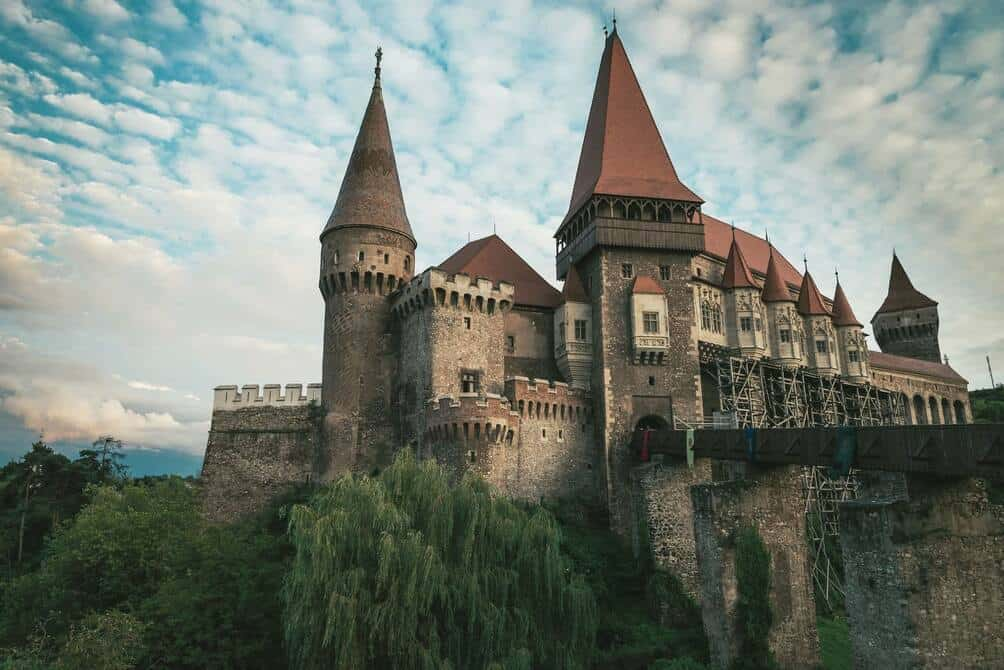 Corvin Castle under blue sky with fluffy scattered clouds.