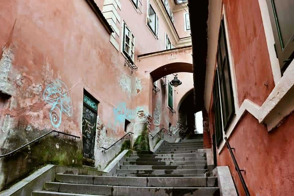 Pink walls line the Goldsmith's Stair Passage in Sibiu with a little graffiti on the left wall.