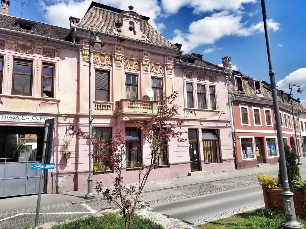Beautiful pink façade of La Cuptor, an excellent date night restaurant in Sibiu, Romania.