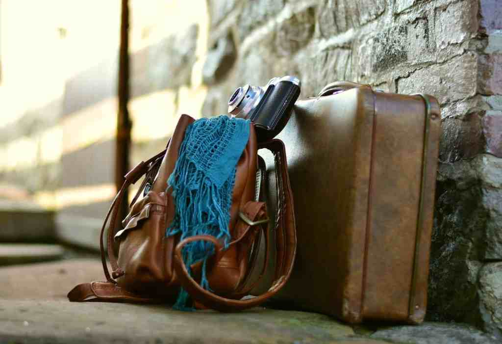 Photo of luggage and bags set against a stone wall.