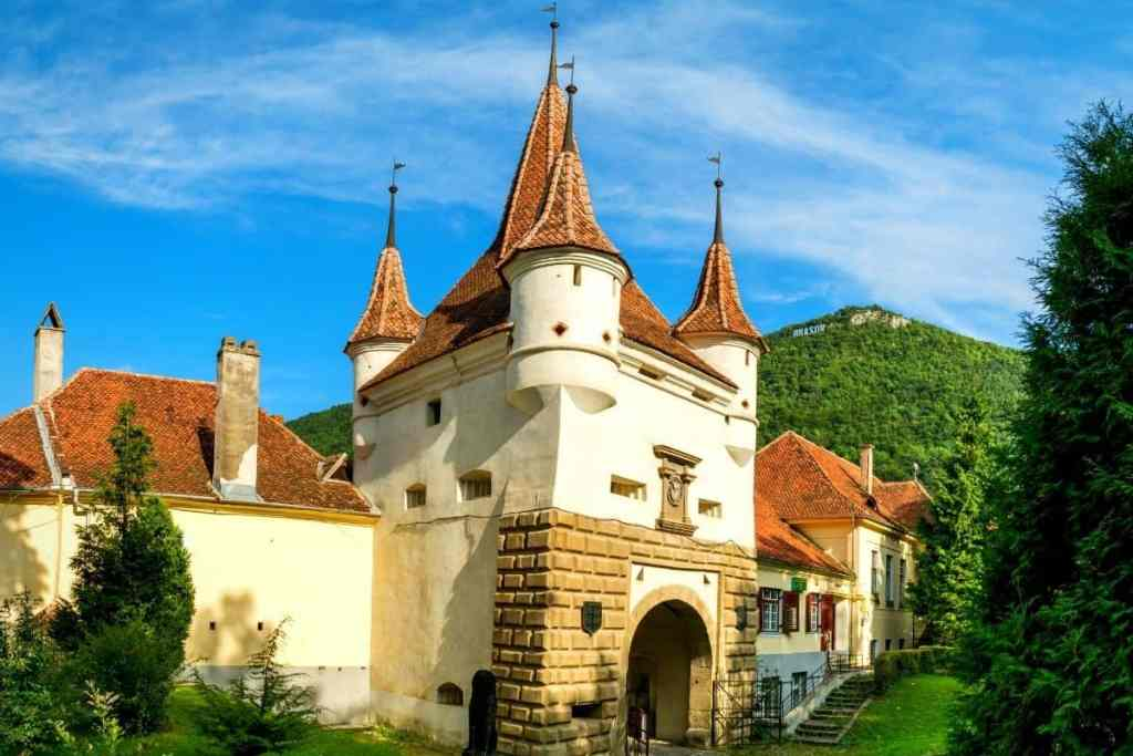 Side view of Catherine's Gate in Brasov, with red spires and a creamy white façade, Tampa mountain seen in the background.