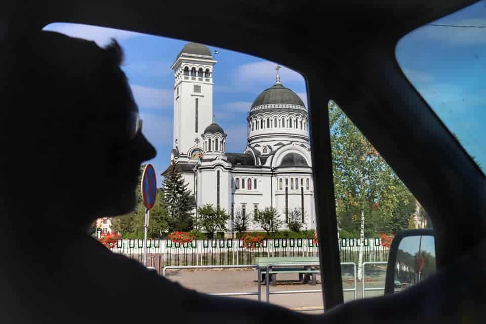 Silhouette of man's face while driving past the Orthodox Cathedral in Sighisoara.