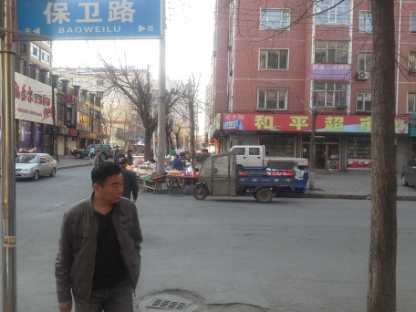 Take a turn right onto BaoWei Lu. Across the street are fruit sellers. In summer.