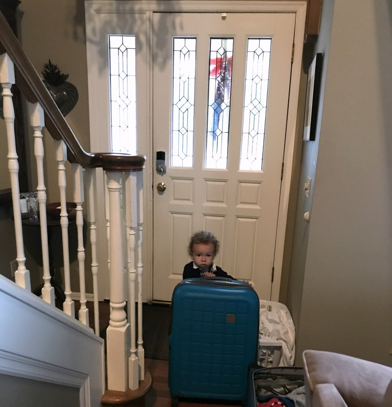 Toddler packing suitcases at Airbnb for families
