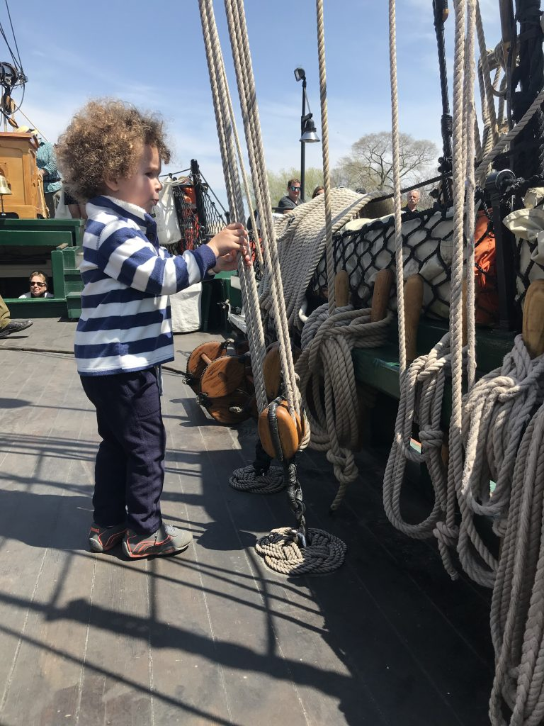 Tulip Time for families, toddler playing with ropes on the Friends Good Will tall ship