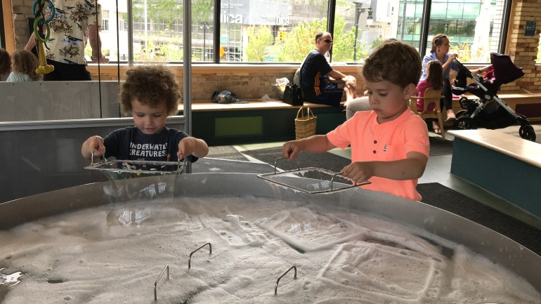 Toddler and Kindergartner at the bubble table at the Grand Rapids Children's Museum-Grand Rapids with Kids post