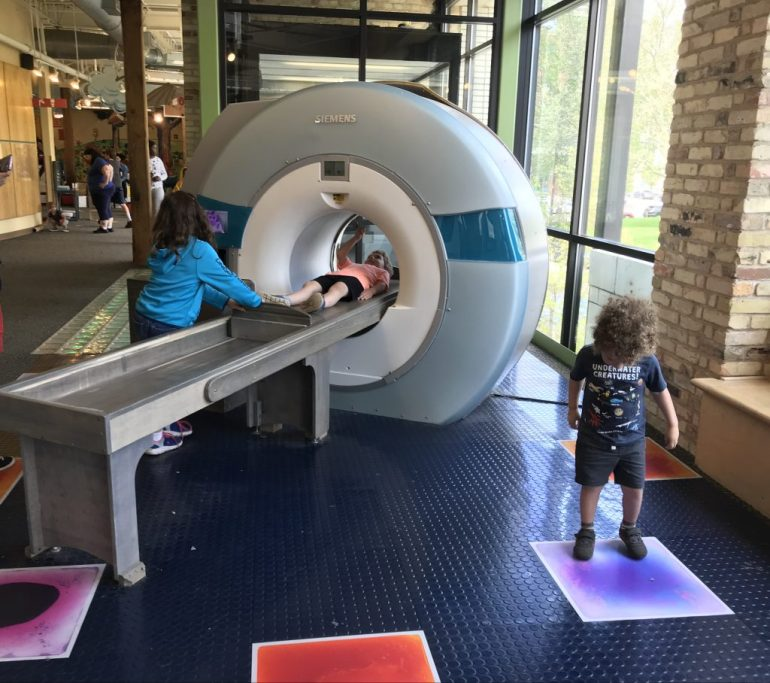Children playing at the MRI machine at the Diagnosis: Fun! exhibit at the Grand Rapids Children's Museum
