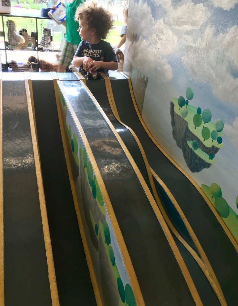 Toddler playing with race track at the Grand Rapids Children's Museum