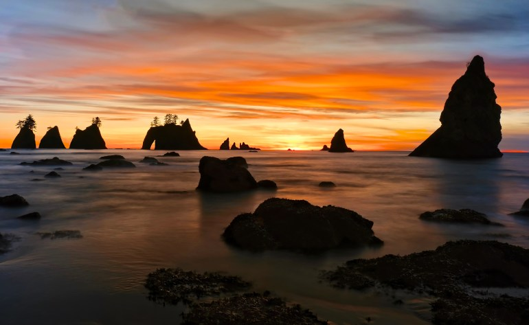 Point of Arches in the Pacific Ocean flanked by a vibrant orange and yellow sunset on Shi Shi Beach in Olympic National Park.
