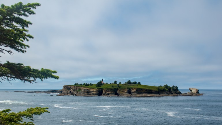 Tatoosh Island, with dramatic cliffs, pine trees, and a lone lighthouse.