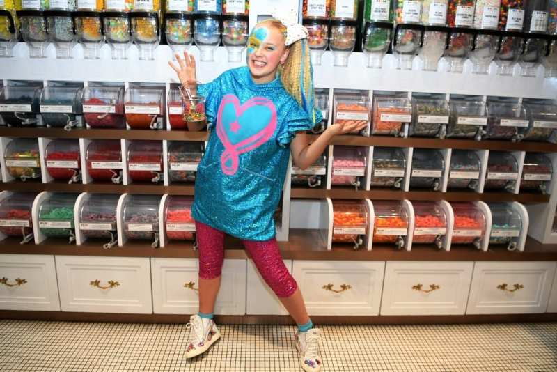 JoJo Siwa poses in the candy store after grabbing some sweet treats.