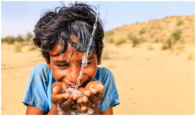 Indian young boy is drinking fresh water, desert village, Thar Desert, Rajasthan, India. Potable water is very precious on the desert - Rajasthani women and children often walk long distances through the desert to bring back jugs of water that they carry on their heads.