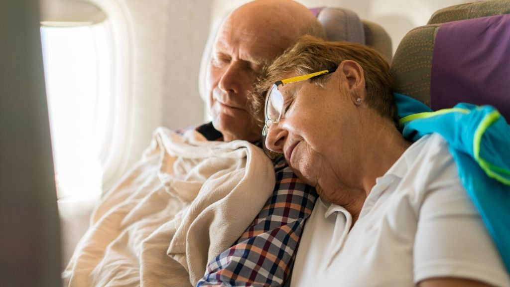 An older couple asleep on an airplane - Tips to Conquer Jet Lag - TravelLatte