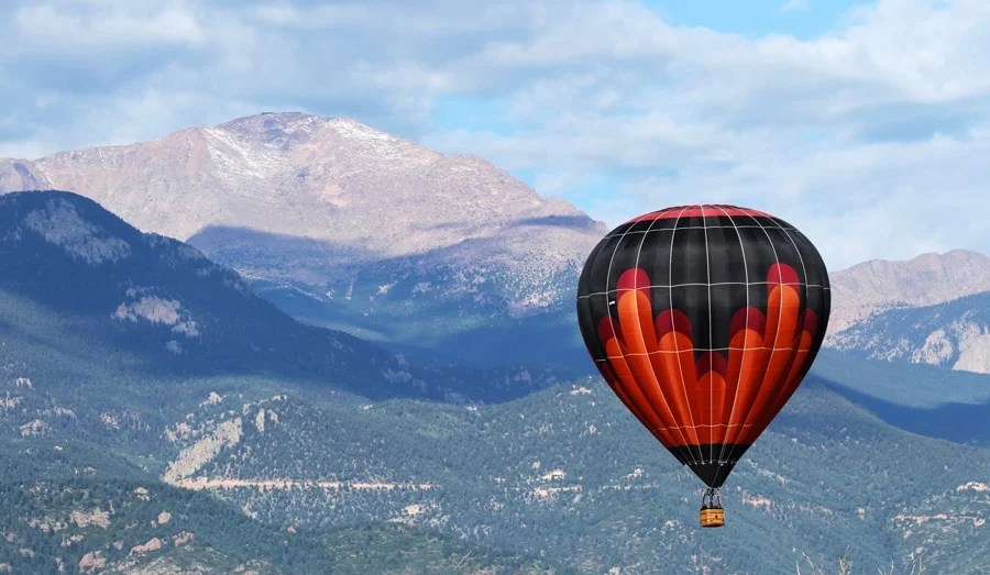 View of a hot air balloon up in the sky of Colorado Springs and mountains on the backgorund