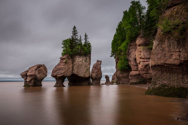 Hopewell rocks tower out of the water while the tide flows in the Bay of Fundy in New Brunswick, Canada