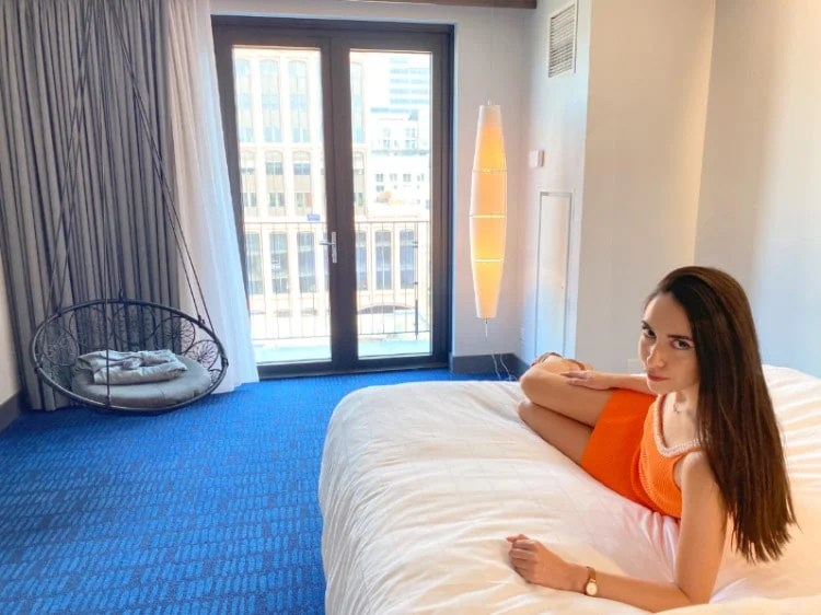 Woman sitting on a bed in The Maven, one of the best hotels in Denver