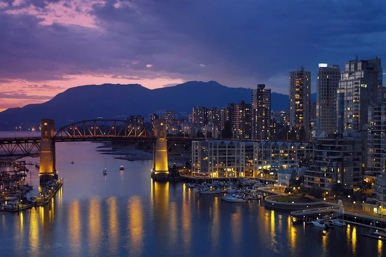 Vancouver, British Columbia at dusk with the sun setting in the background and city lights reflecting on the water