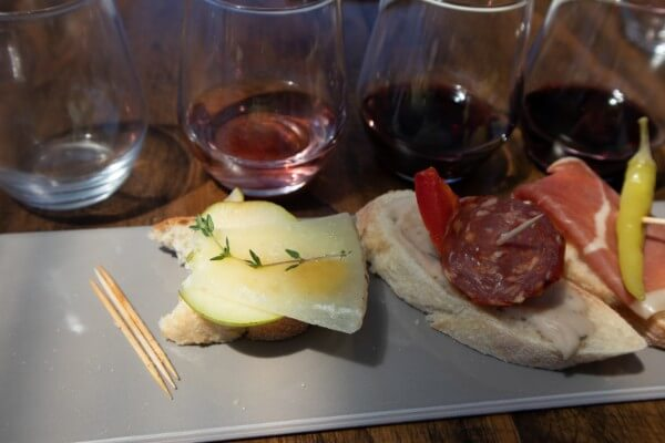 close-up-of-a-rectangle-plate-with-three-pintxos-matched-with-three-wines-on-a-wooden-table-at-pandemonium-wine-estate-swan-valley