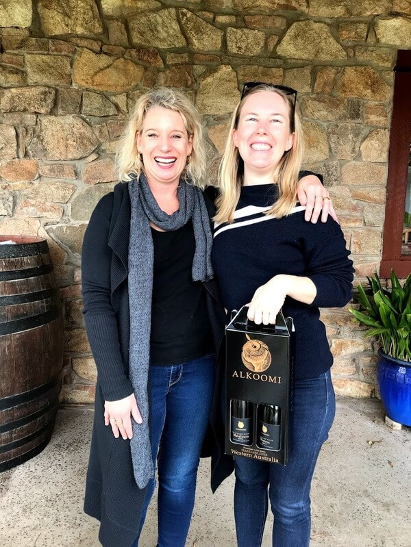 sandy-of-alkoomi-winery-with-her-arm-around-naomi-of-the-travelling-corkscrew-while-holding-a-box-with-a-bottle-of-melaleuca-and-victrix-white-wine-in-frankland-river-great-southern