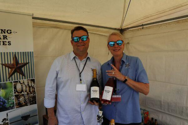 paul and gewn of rising star wines holding a bottle of sparkling wine and brose at the albany wine and food festival