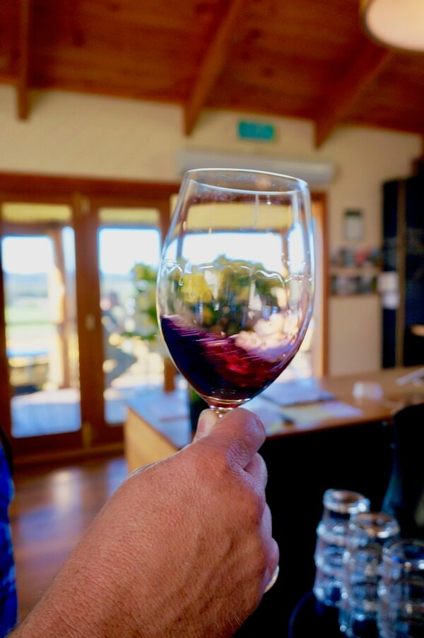 Swirling red wine at Moores Hill - Tamar Valley, Tasmania