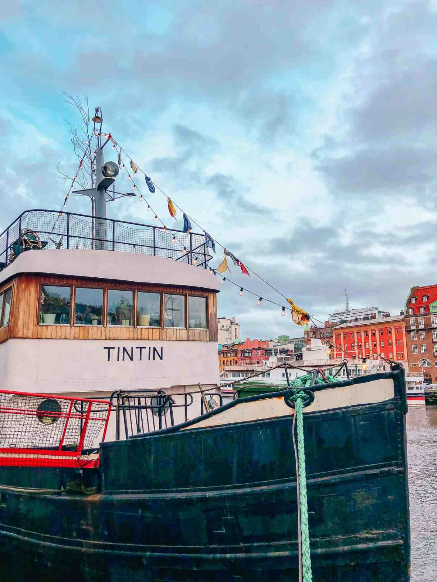 Tintin boat on harbour with coloured buildings