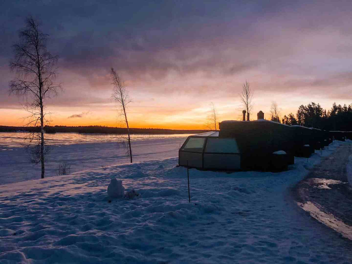 A row of glass igloos in front of the sun rising over a frozen lake