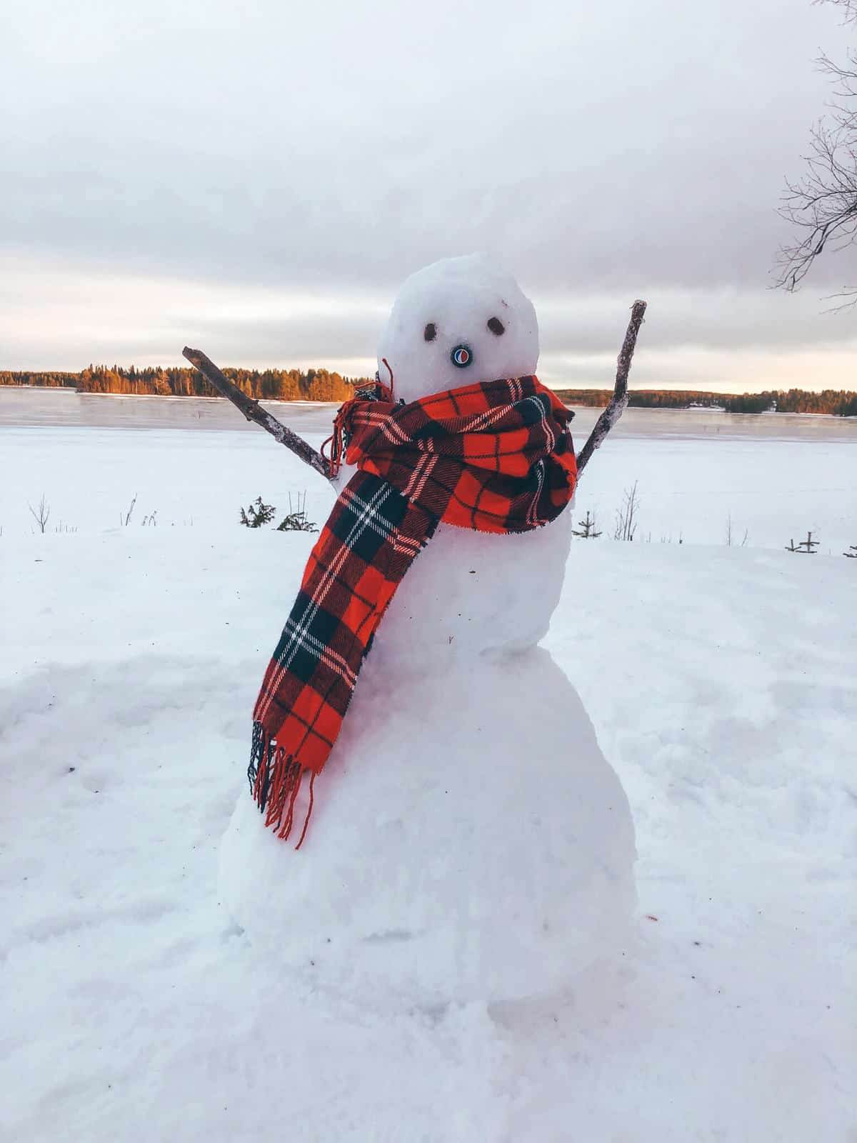 A snow man wearing a red tartan scarf in front of a frozen lake