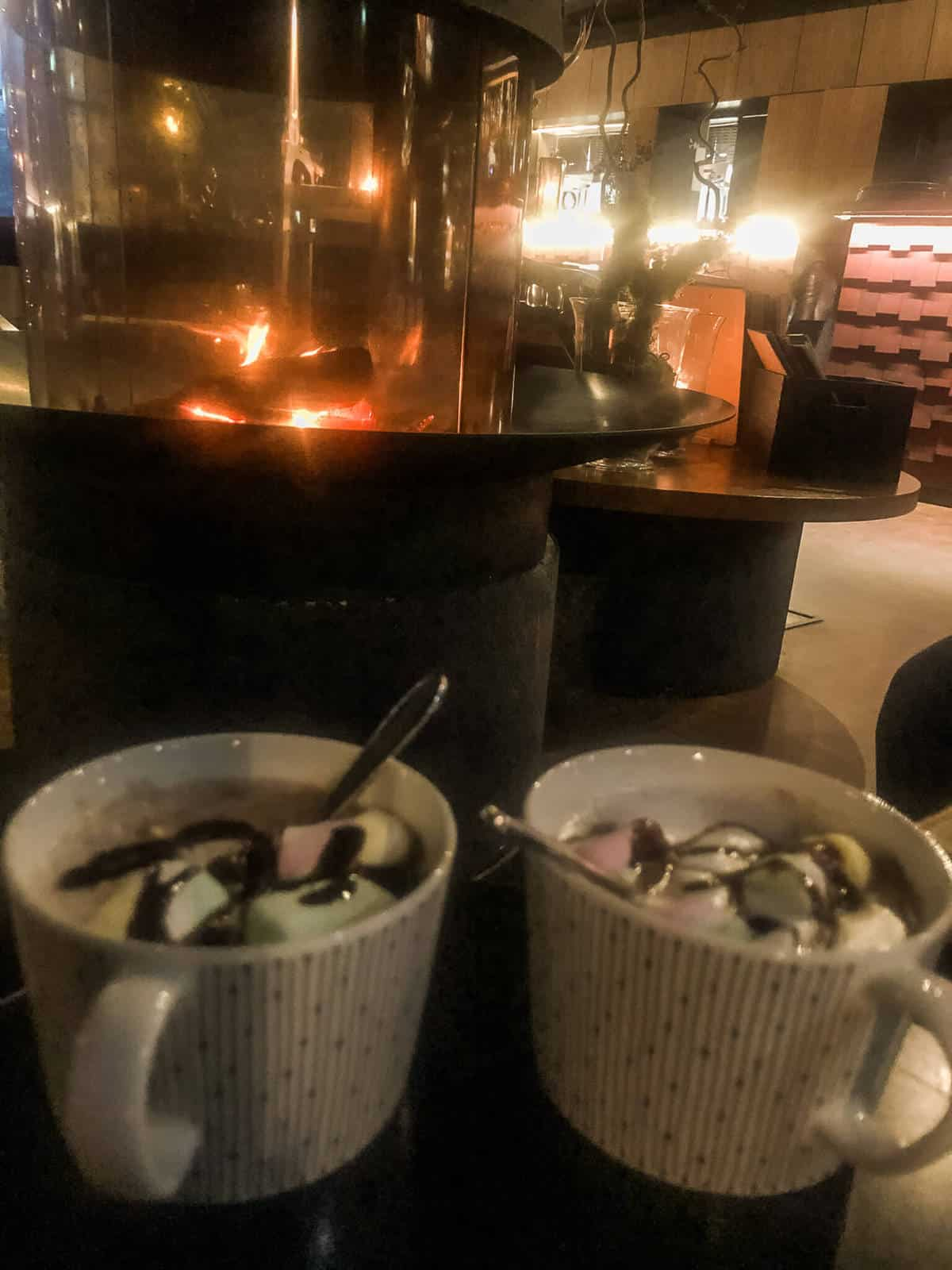 Two mugs of hot chocolate and marshmallows in front of a fire