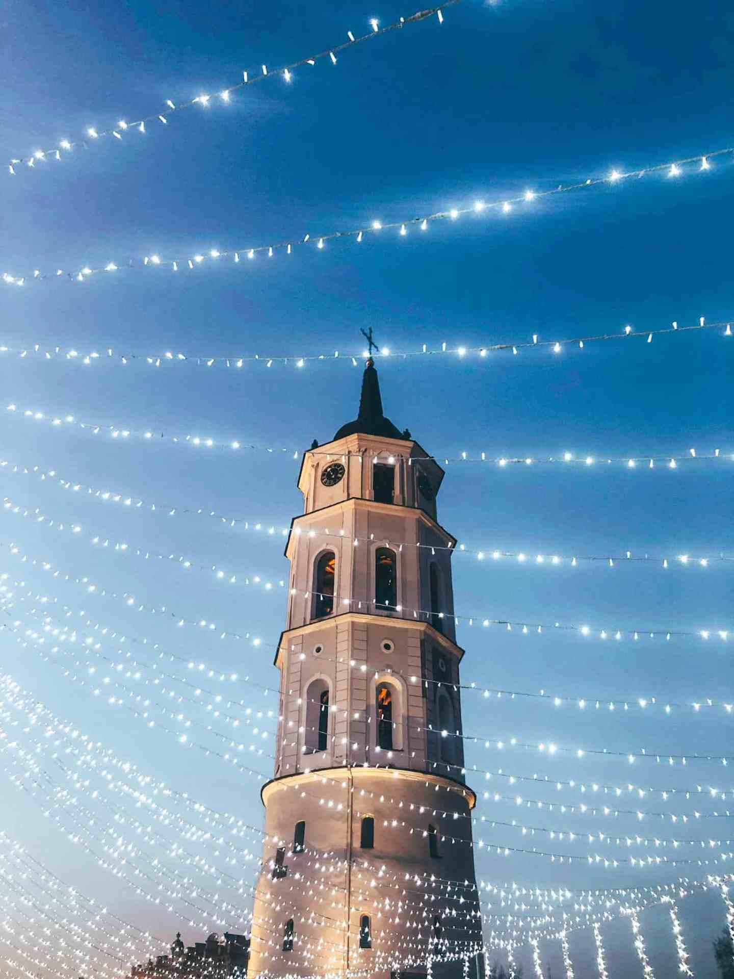 A bell tower covered in fairy lights
