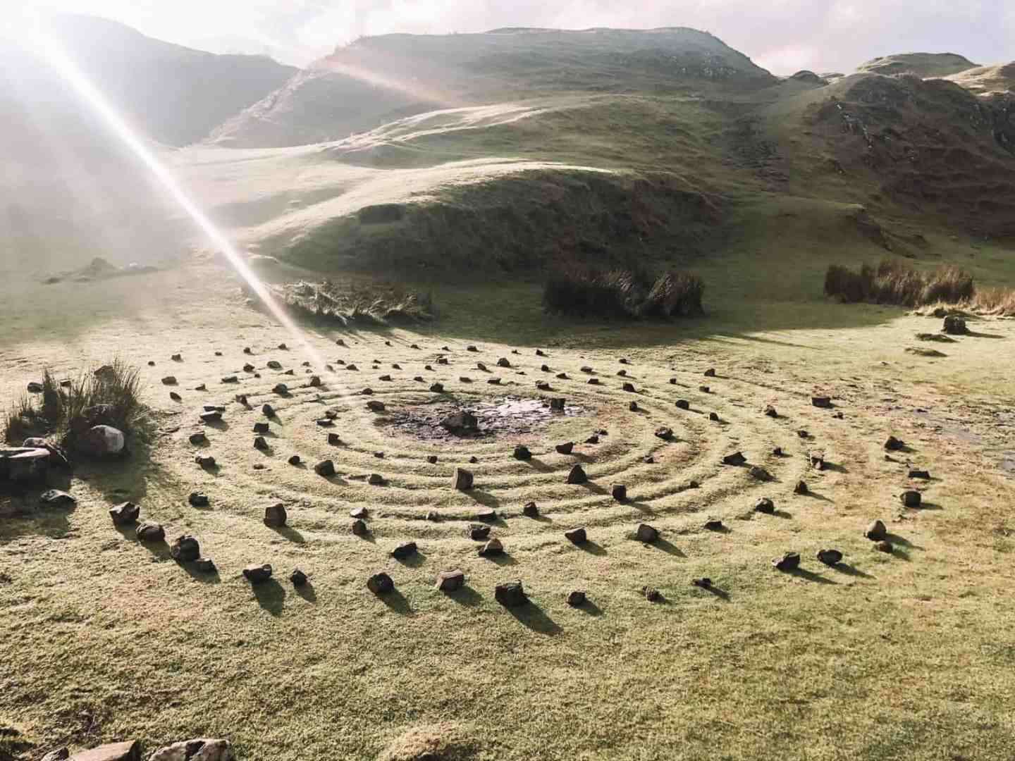 The sunsetting over a grassy field surrounded by rocks and a rock circle in the middle of the field