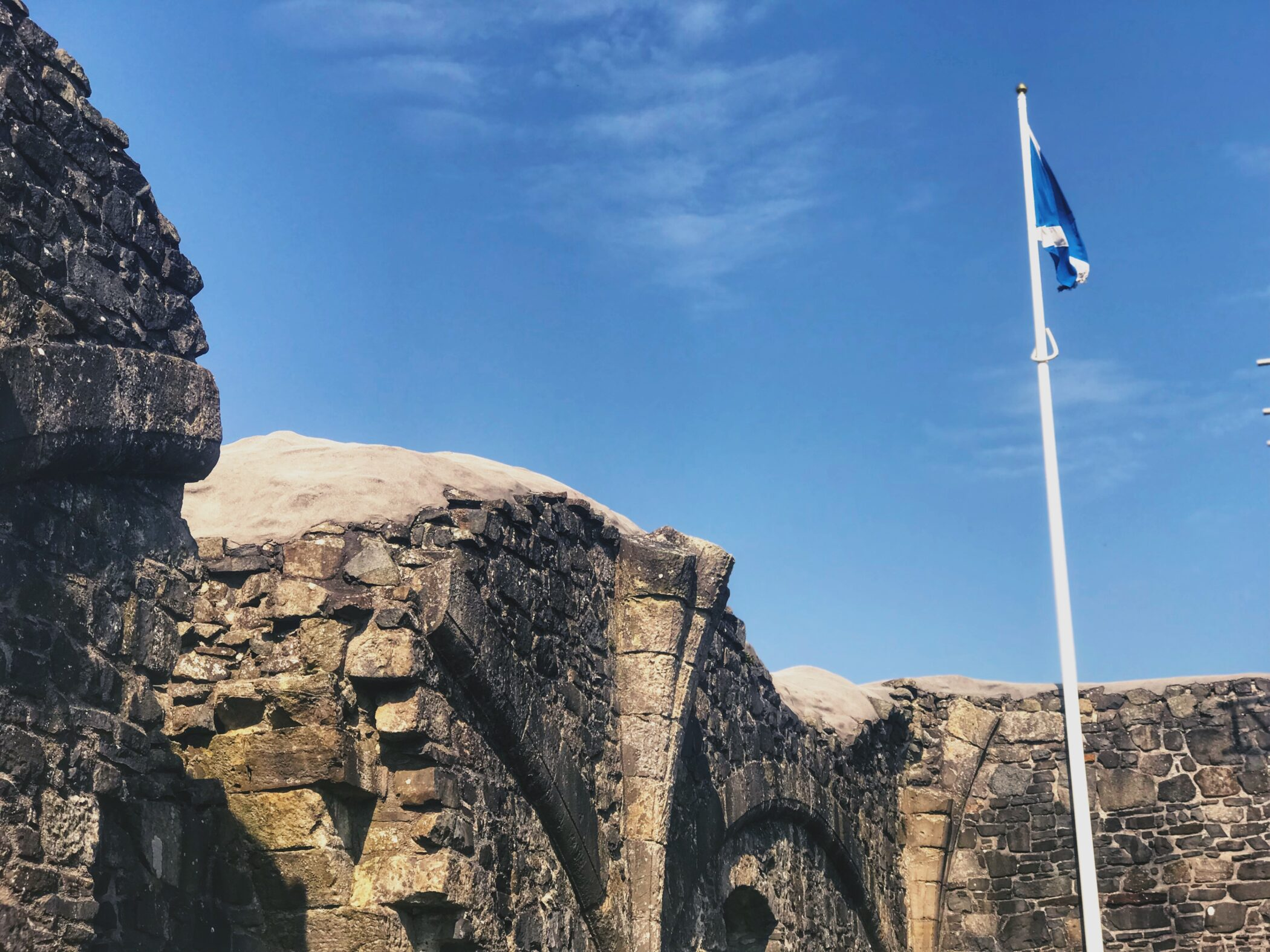 The top of Dundonald castle with a Scottish flag flying against the blue sky