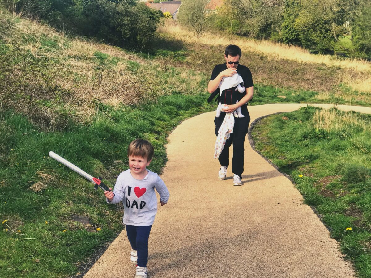 Neil, cary baby Felix and Dexter, carrying a plastic sword walking up the beige path to Dundonald castle