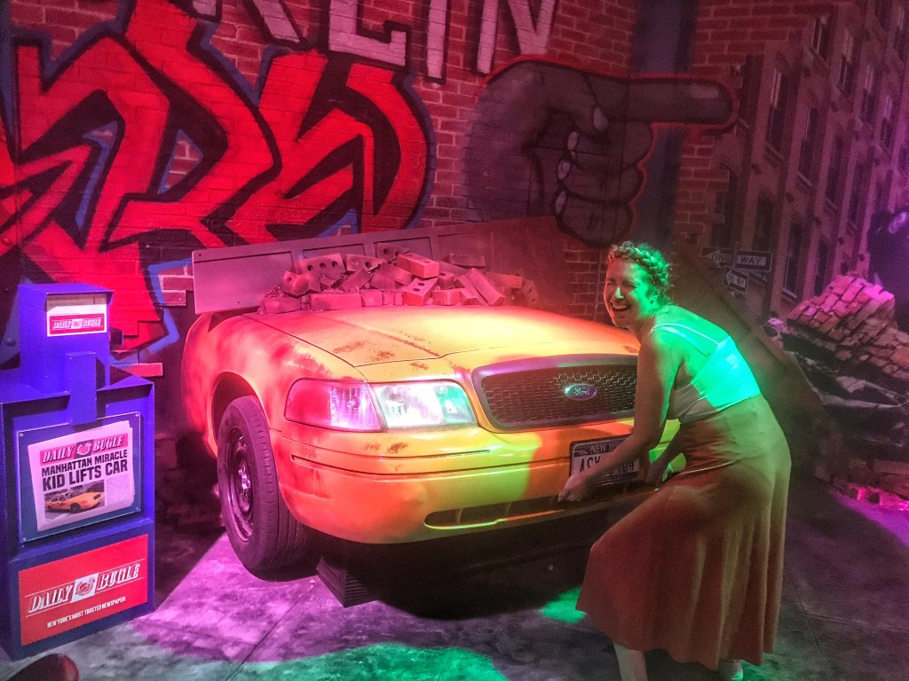 Nicola lifting a yellow tax in the MARVEL SUPER HEROES area at Madame Tussauds Blackpool
