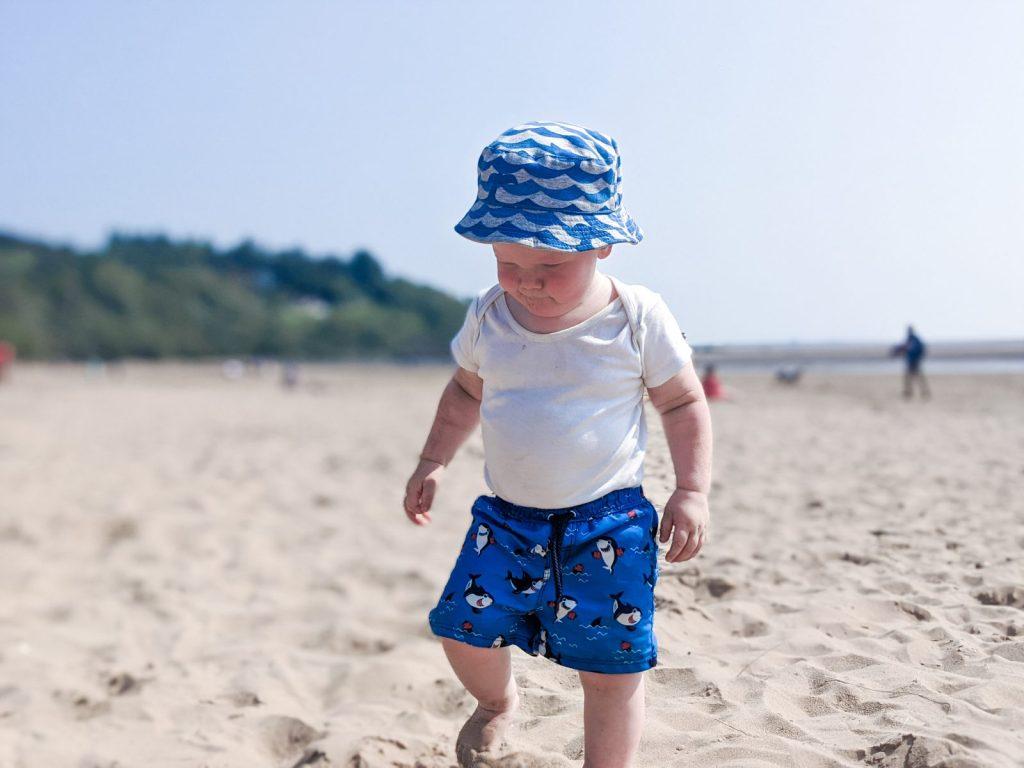 Felix walking over the sand at Sandyhills beach