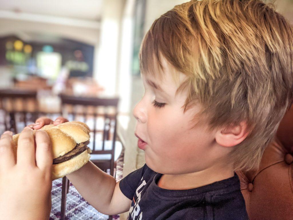 Dexter eating burger at Jolly Harvester
