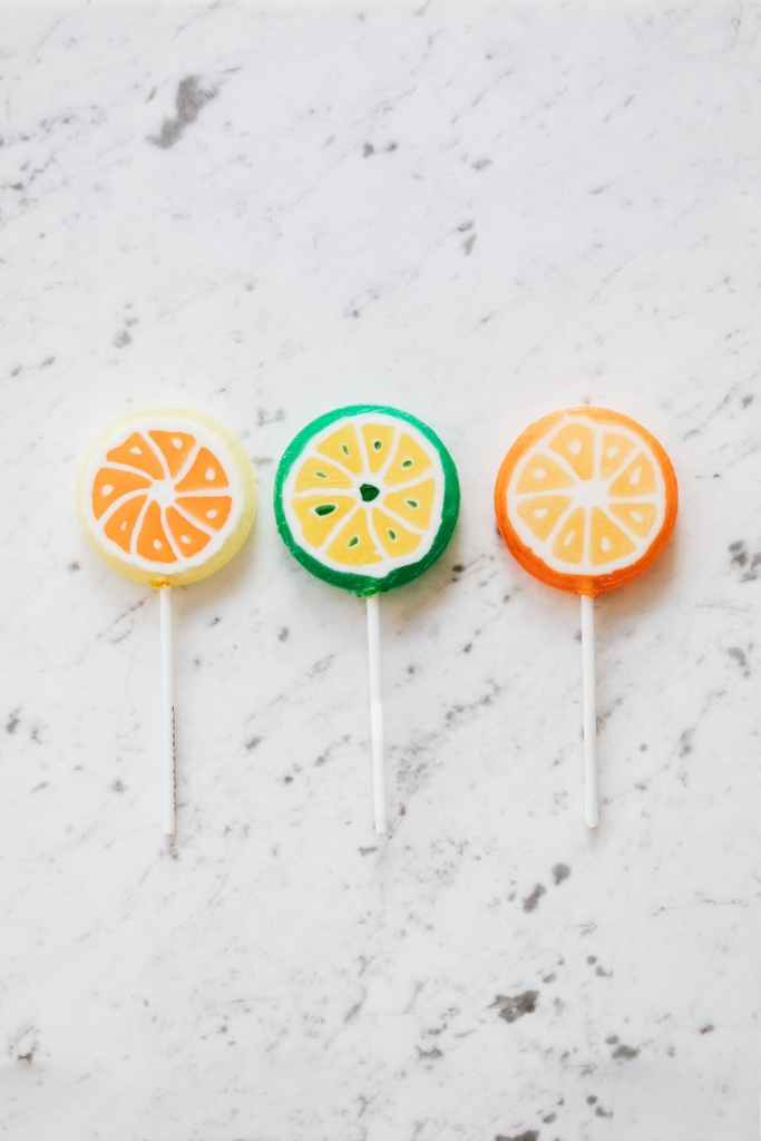 assorted colorful lollipops on marble surface