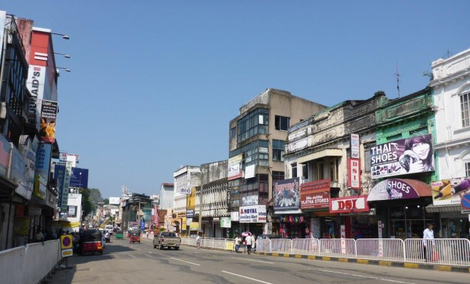 One of the main streets in Kandy, with plenty of commercial signs .