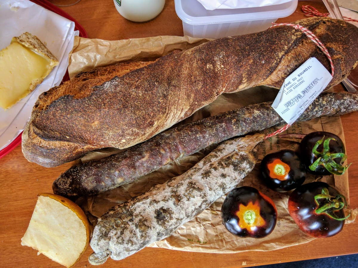 Baguette, sausages and black tomatoes