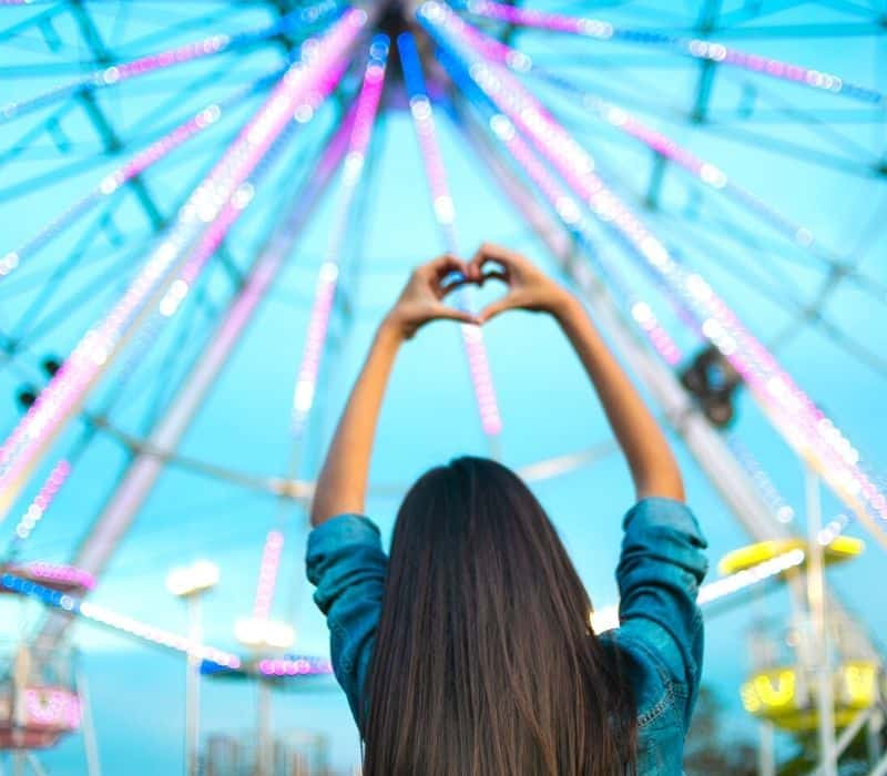 Woman in front of ferris wheel making heart shape with her hands