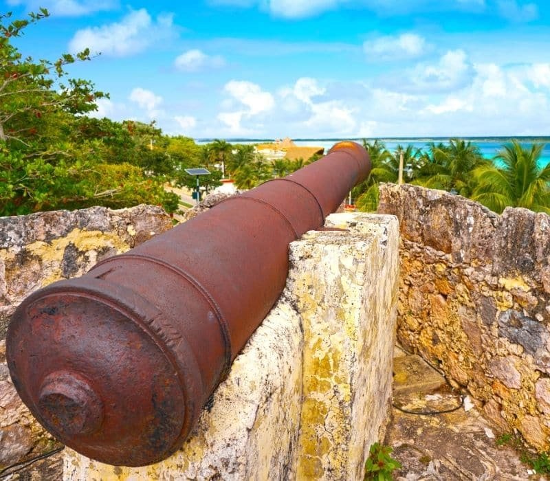 rusted cannon at a fort pointed at the beach