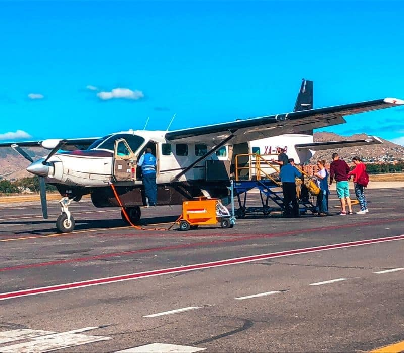 people boarding a small plane - Traveling to Oaxaca
