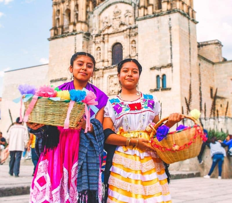 two girls in front of a cathedral in traditional dress holding baskets in oaxaca mexico - Traveling to Oaxaca